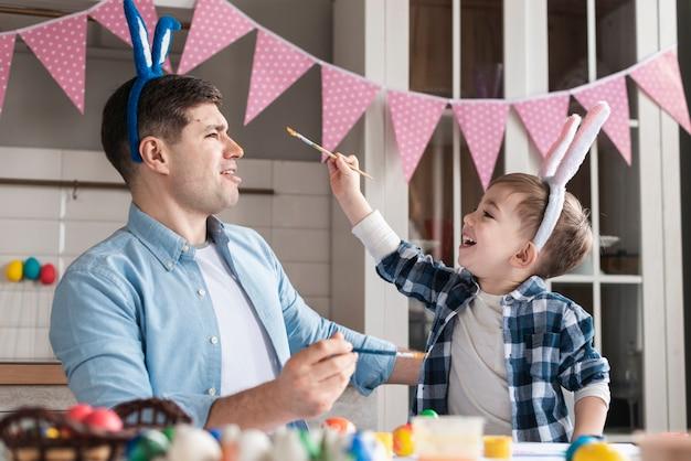 Mały chłopiec próbuje namalować ojca