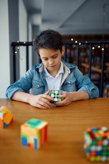 Mały chłopiec próbuje rozwiązać kostki puzzle. zabawka do treningu mózgu i logicznego umysłu, kreatywna gra, rozwiązywanie złożonych problemów