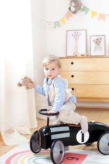 Mały chłopiec prowadzący pedał samochodowy w pokoju dziecinnym. szczęśliwe dziecko jazda zabawka rocznika samochodu. zabawne dziecko grające w domu. koncepcję wakacji letnich i podróży. berbeć jedzie retro samochód, chłopiec w zabawkarskim samochodzie. dzieciństwo