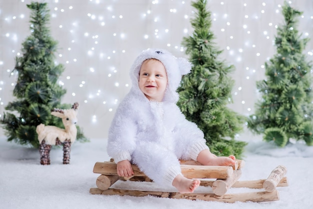 Mały chłopiec przebrany za białego niedźwiedzia polarnego siedzi wśród lasu choinek na drewnianych saniach.