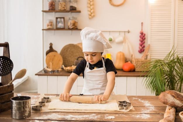 Mały chłopiec przebrany za szefa kuchni rozwałkowuje ciasto drewnianym wałkiem przy kuchennym stole