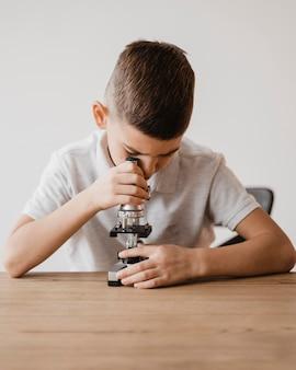 Mały chłopiec przy użyciu mikroskopu do nauki