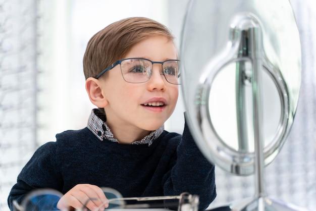 Mały chłopiec przymierza okulary w sklepie