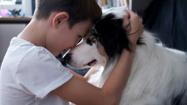 Mały chłopiec przytula się z australijskim pasterzem merle