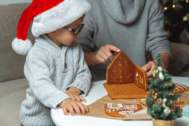 Mały chłopiec razem z mamą dekorują świąteczny domek z piernika