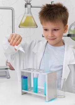 Mały chłopiec robi eksperyment naukowy w szkole