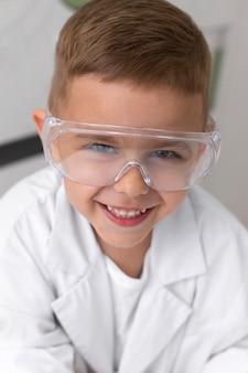 Mały chłopiec robi eksperyment w szkole