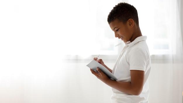 Mały chłopiec robi notatki z domu