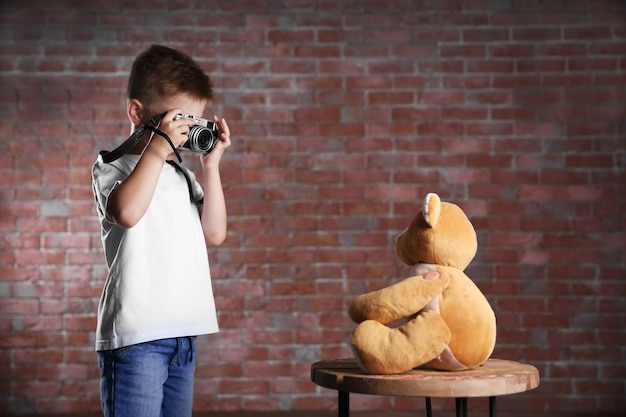 Mały chłopiec robienia zdjęć niedźwiedzia zabawka na mur z cegły