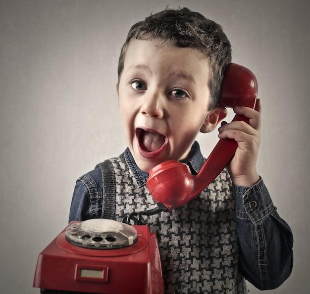 Mały chłopiec rozmawia na klasyczny czerwony telefon