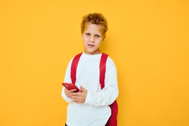 Mały chłopiec rozmawia przez telefon na żółtym tle szkolnego plecaka