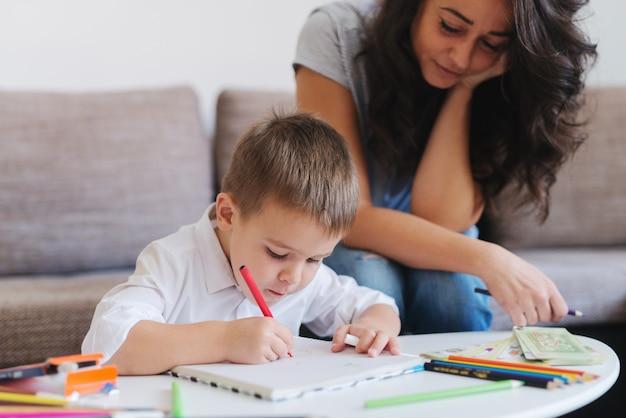Mały chłopiec rysowanie kredkami, podczas gdy jego matka siedzi na kanapie i patrzy na niego. selektywna koncentracja na dziecku. wnętrze domu