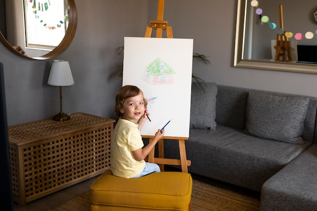 Mały chłopiec rysujący za pomocą sztalugi w domu