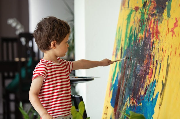 Mały chłopiec rysuje i maluje pędzlem i farbami w domu