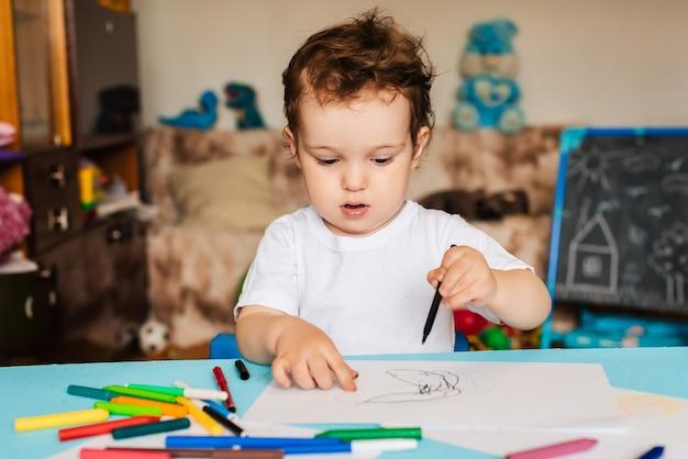 Mały chłopiec rysuje kredkami na kartkach leżących na stole