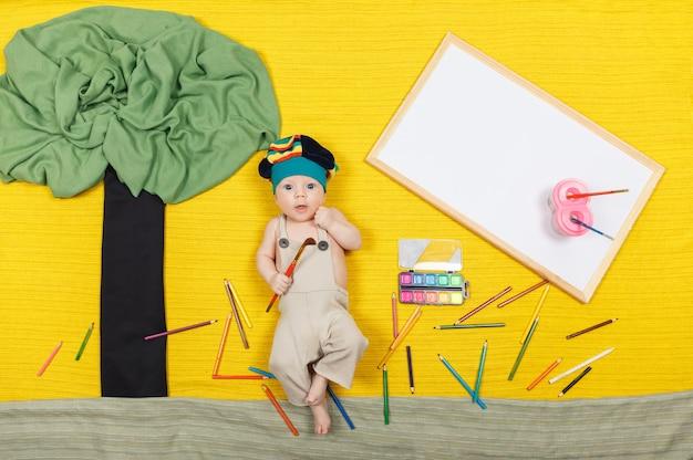 Mały chłopiec rysunek dzieła sztuki. przystojny dziecko leżące na żółtej powierzchni