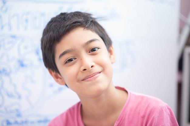 Mały chłopiec rysunek eart na tablicy w pokoju