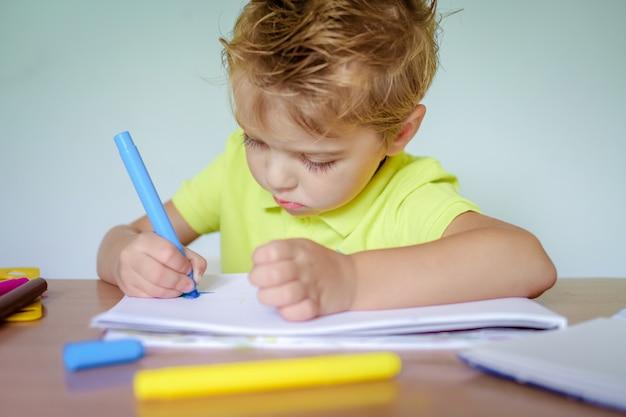 Mały chłopiec rysunek kredkami kolor