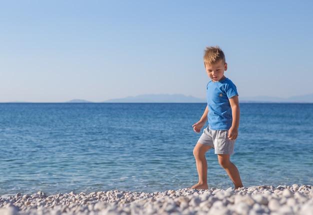 Mały chłopiec rzuca kamieniami w morze. letnia koncepcja wakacji i niewinności. beztroskie dzieciństwo.