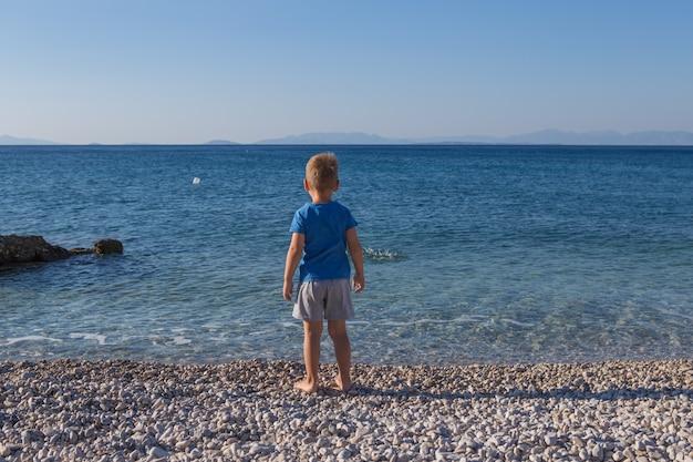 Mały chłopiec rzuca kamieniami w morze, widok z tyłu. letnia koncepcja wakacji i niewinności. beztroskie dzieciństwo.