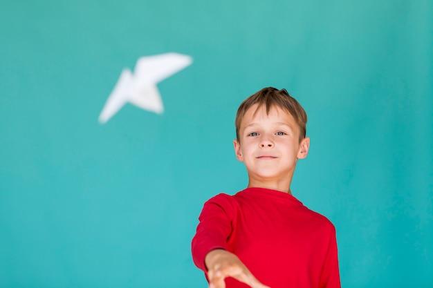 Mały chłopiec rzuca papierowy samolot