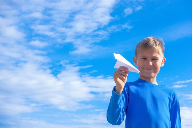 Mały chłopiec rzuca papierowym samolotem