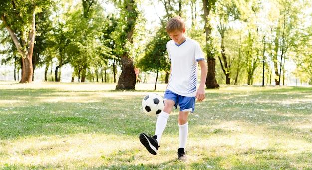 Mały chłopiec sam gra w piłkę nożną