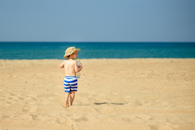 Mały chłopiec samotnie bawi się nad brzegiem morza w czapce i pasiastych szortach heat