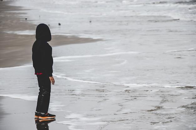 Mały chłopiec samotnie nad oceanem