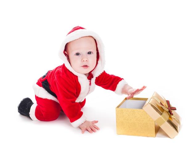 Mały chłopiec santa ze złotymi pudełkami prezentowymi na białym tle