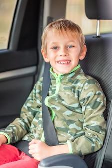 Mały chłopiec siedzący na podwyższeniu zapięty pasami w samochodzie. bezpieczeństwo fotelika samochodowego dla dzieci