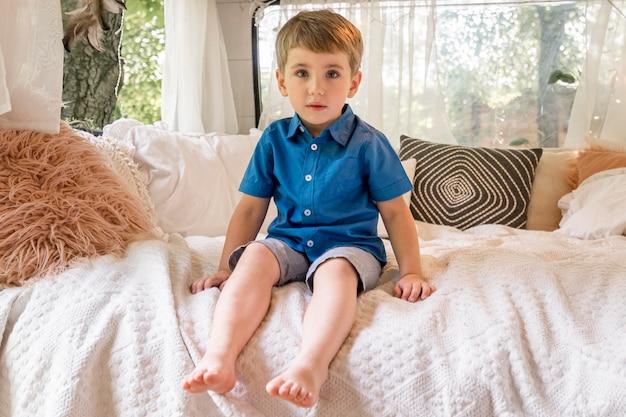 Mały chłopiec siedzący w swojej przyczepie kempingowej