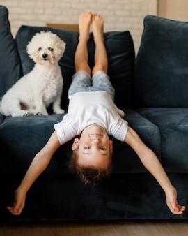 Mały chłopiec siedzący z głową w dół na sofie