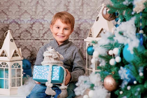 Mały chłopiec siedzący z prezentem świątecznym w pobliżu choinki i ozdób choinkowych