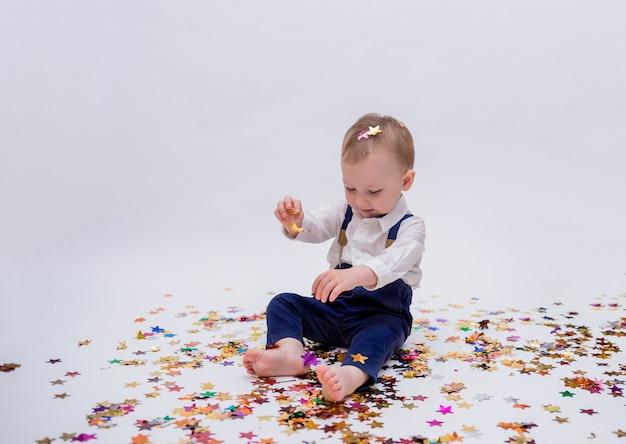 Mały chłopiec siedzi i gra z konfetti na białym na białym tle
