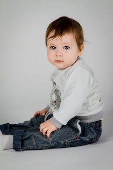 Mały chłopiec siedzi na białym tle