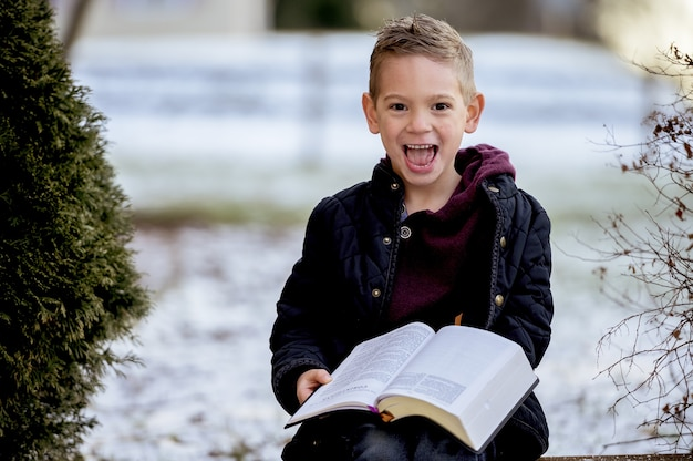 Mały chłopiec siedzi na drewnianych deskach i czyta biblię w ogrodzie pokrytym śniegiem