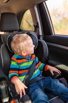 Mały chłopiec siedzi na foteliku samochodowym zapięty w samochodzie. bezpieczeństwo fotelika samochodowego dla dzieci
