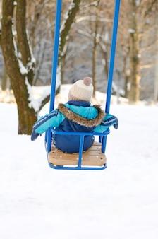 Mały chłopiec siedzi na huśtawce, piękna pogoda zimowy dzień widok z tyłu