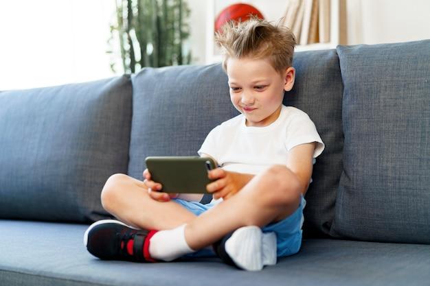 Mały chłopiec siedzi na kanapie w domu i przy użyciu smartfona