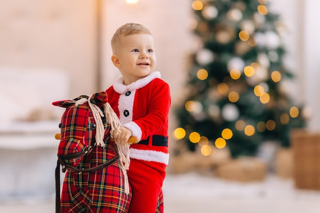 Mały chłopiec siedzi na koniku na biegunach i uśmiech. niewyraźne choinki