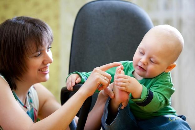Mały chłopiec siedzi na krześle komputera. dziewczyna trzyma stopy dziecka w ręku. niewyraźne tło na zdjęciu