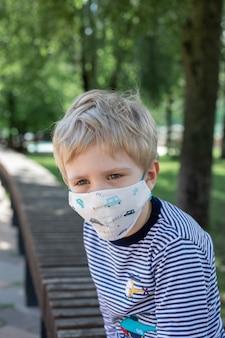 Mały chłopiec siedzi na ławce w parku w masce ochronnej