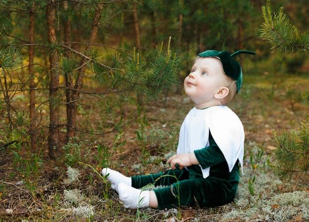 Mały chłopiec siedzi na leśnej ścieżce w stroju przebiśnieg. chłopcy ubrani w zabawny kostium przebiśnieg z kapeluszem