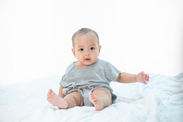 Mały chłopiec siedzi na łóżku