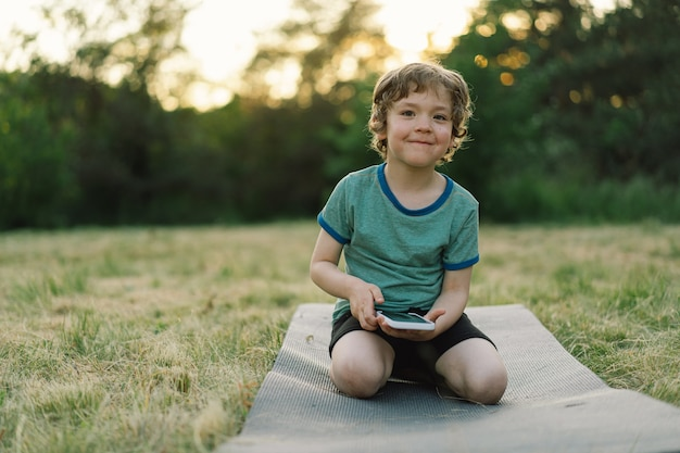 Mały chłopiec siedzi na macie sportowej w plenerze i używa koncepcji stylu życia w telefonie komórkowym