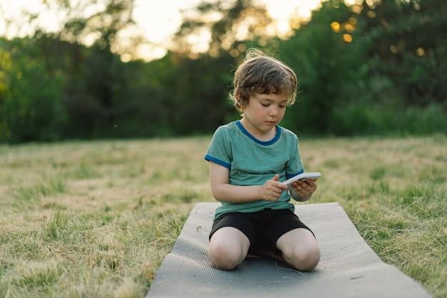 Mały Chłopiec Siedzi Na Macie Sportowej W Plenerze I Używa Koncepcji Stylu życia W Telefonie Komórkowym Premium Zdjęcia