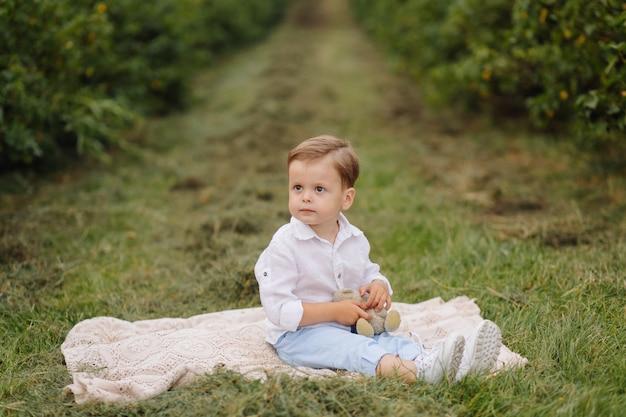 Mały chłopiec siedzi na piknik w kratę w ogrodzie