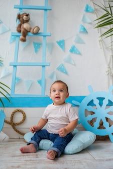 Mały chłopiec siedzi na podłodze obok drewnianej łodzi
