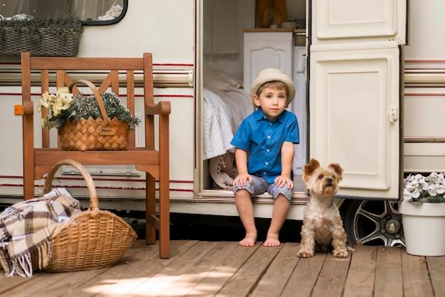 Mały chłopiec siedzi na przyczepie kempingowej obok uroczego psa